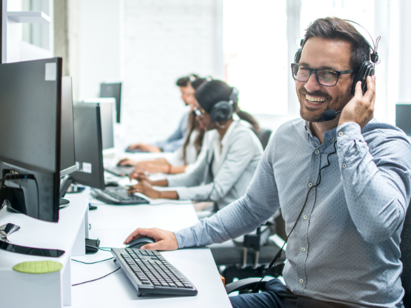 Smiling man with headset at computer desk answering phones, others sitting behind him doing the same
